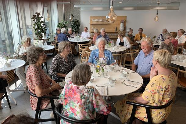 Bilde av glade mennesker på seniorlunsj