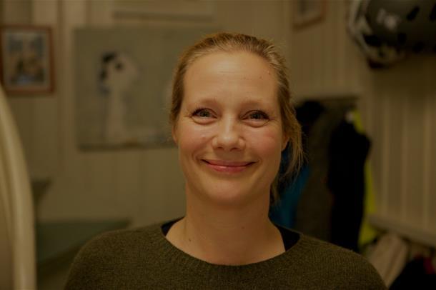 En kvinne ser inn i kamera og smiler