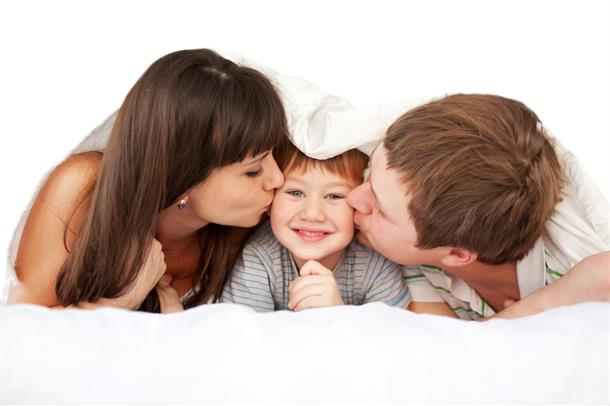 Et barn ligger mellom to voksne og får et kyss på hvert kinn