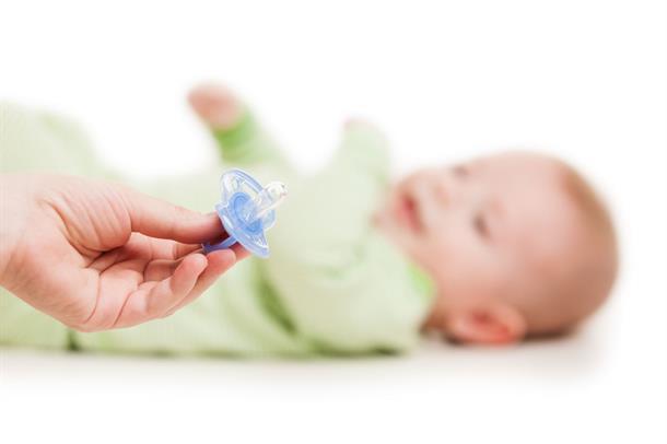 En voksen hånd holder ut en smokk foran ansiktet til et lite barn