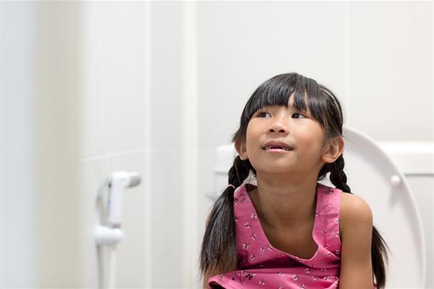 En liten jente sitter på et toalett