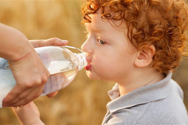 En liten gutt med rødt hår drikker vann fra en flaske