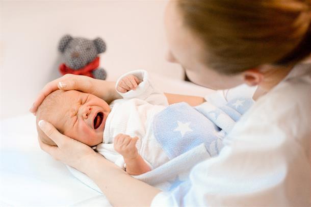 En barnepleier steller et barn.