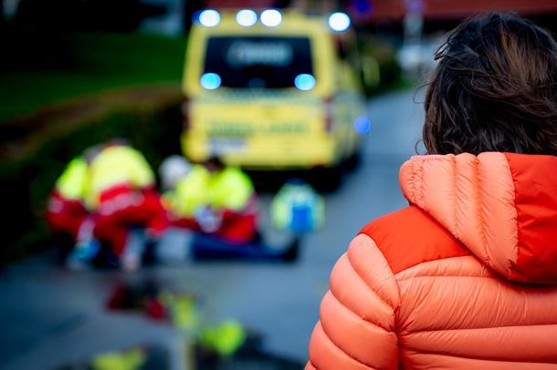 Ambulansepersonell gir førstehjelp til person på bakken. Kvinne står alene og ser på.